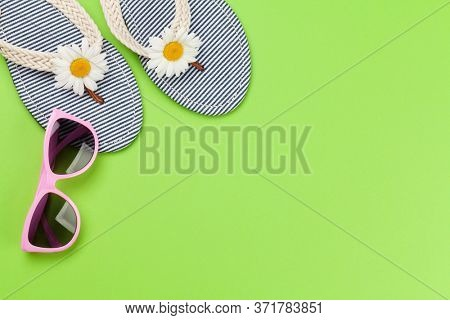 Beach flip flops with flowers and sunglasses on green background. Summer vacation concept. Flat lay with copy space
