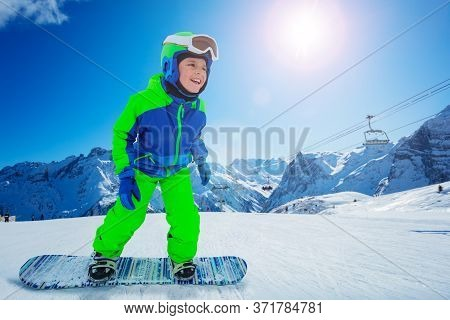 Side Close Portrait Of A Boy On Snowboard Move Fast Downhill Smile And In Active Pose Over Ski Lift,