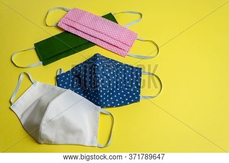 Four Colored Different Reusable Medical Masks On Yellow Isolated Background. Hygienic Antimicrobial,