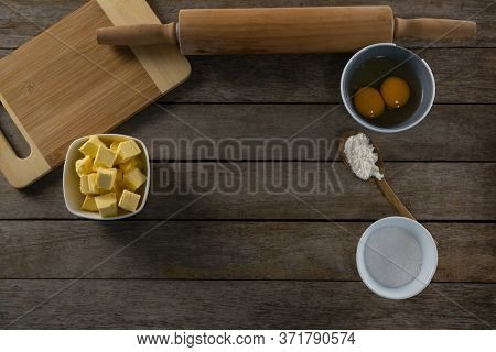 Overhead view of cheese cubes and egg yolk on a wooden table