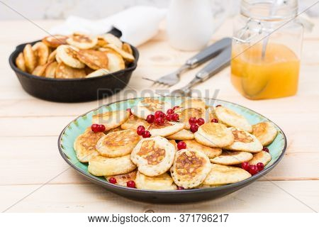 Trend Breakfast. Dutch Mini Pancakes With Red Currants On A Plate And A Pan With Them On A Wooden Ta