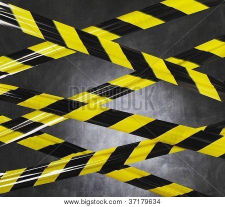 Fita de barreira plástica preta e amarela bloqueando o caminho.