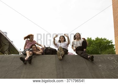 A Group Of Four Fashionable Teenager Friend Girls Are Sitting, Laughing, Smiling And Indulging In Th