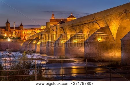 Ancient Roman Bridge In Cordoba With  Cordoba Mosque And Cathedral In The Background