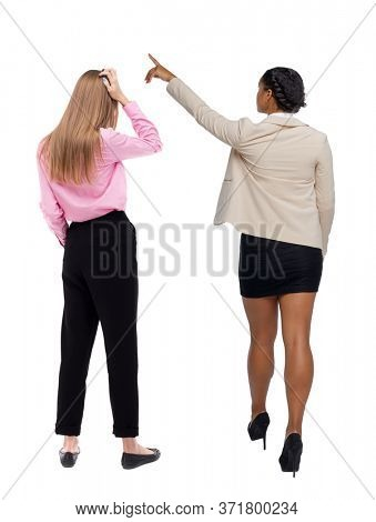 Back view of  two business woman in suit pointing. Business team. Rear view people collection. backside view of person. Rear view. Isolated over white background.