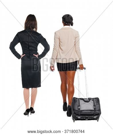 Back view of  two business women in suit pointing. Business team. traveling with suitcas. Back view. Rear view people collection. backside view of person. Isolated over white background.