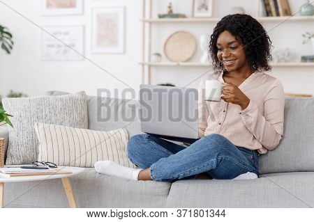 Leisure Concept. Young Woman Relaxing At Home On The Couch, Having Coffee And Using Laptop Computer,