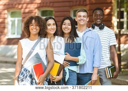 College Community. Group Of Smiling Multi-ethnic Students Posing At Campus, Holding Workbooks And Sm