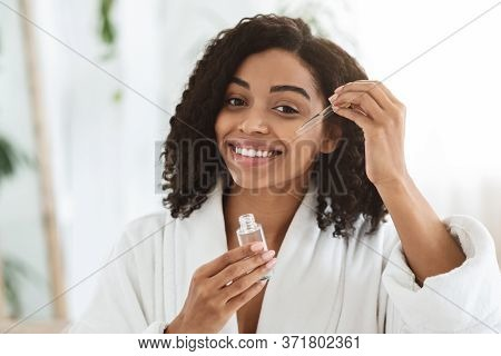 Smiling Afro Woman Applying Hydrating Face Serum On Her Beautiful Skin, Pampering Herself After Show