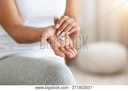 Closeup Of Unrecognizable Black Woman With Moisturising Cream On Her Hands, Cropped Image With Selec