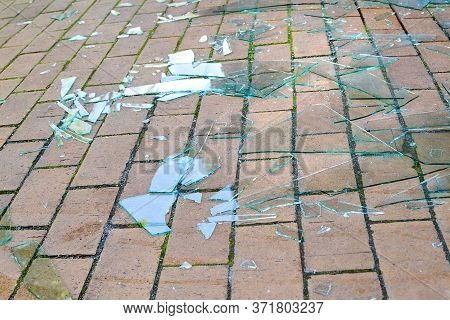 Shards Of Broken Glass. Pieces Of Broken Glass On The Paving Stones. The Concept Of Destruction. Ima