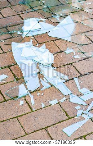 Broken Glass. Shards Of Broken Glass On The Paving Stones. The Concept Of Destruction. Image For Edi