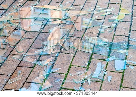 Broken Glass. Shards Of Glass On The Paving Stones. The Concept Of Destruction. Image For Editing An