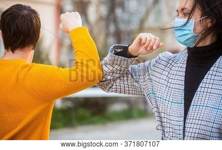 Elbow Bump. Coronavirus, Illness, Quarantine, Medical Mask, Covid19. Couple Greeting With Elbows. El
