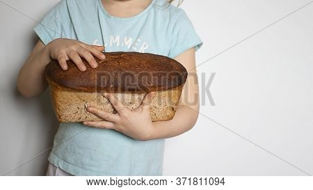 Kid Holding In Hands Big Fresh Loaf Of Homemade Premium Rye And Wheat Flour Bread On White Backgroun