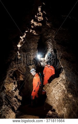 Two Men, Strong Physique, Explore The Cave. Men Dressed In Special Clothes To Pass Through The Cave