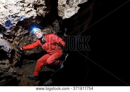 Man Walking And Exploring Dark Cave With Light Headlamp Underground.