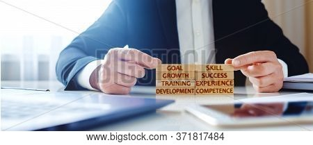 Business Training Concept. Man Stacks Wooden Blocks With The Inscriptions Development, Experience, T