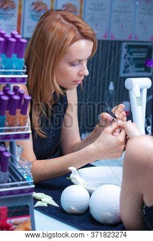 master in the salon applies nail polish