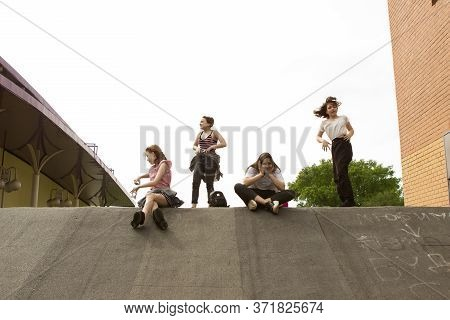 A Group Of Four Fashionable Teenage Girls Jumping, Having Fun, Laughing, Smiling And Indulging In Th