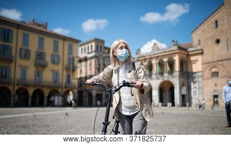 Mature masked woman riding her e-bike in a city during Coronavirus pandemic