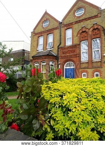 English Street With Typical Brick Houses And Front Gardens In Front Of Them