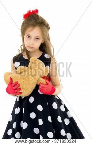 Pretty Long Haired Girl Wearing Polka Dot Dress Standing With Teddy Bear, Length Portrait Of Lovely