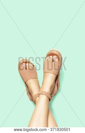 Female Legs With White Pedicure In Summer Brown Sandals On Background, Copy Space