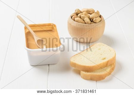 Two Slices Of Bread, Peanut Butter, And Peanuts On A White Table. Natural Peanut Cream.