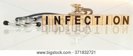 Infection The Word On Wooden Cubes, Cubes Stand On A Reflective White Surface, On Cubes - A Stethosc