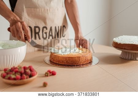 Man Pastry Chef Put Icing Cream On Sponge Cake. Making Sponge Cake Series