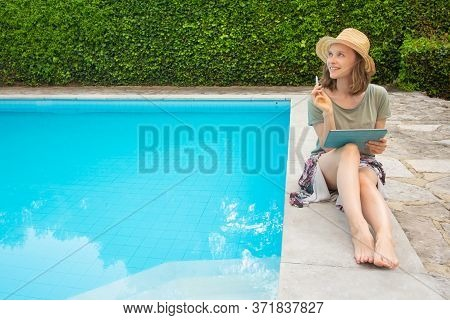 Pensive Inspired Woman With Tablet And Stylus Thinking Over Ideas While Sitting And Working At Swimm