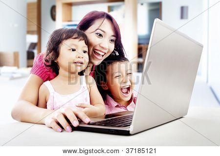 Familia feliz con el portátil en casa
