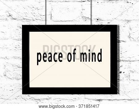 Black Wooden Frame With Inscription Peace Of Mind Hanging On White Brick Wall