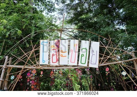 A Signboard Of Oh Poi Market In Thai Language On A Bamboo Pole,a Famous Local Market In Suan-phueng,