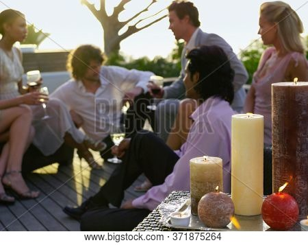 Friends sitting on porch Drinking and socialising near candle arrangement