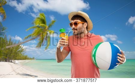 summer holidays, vacation and travel concept - happy young man in sunglasses and straw hat with orange juice cocktail and inflatable beach ball over tropical beach background in french polynesia