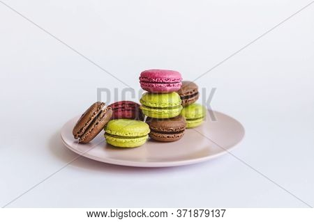 Set Of Tasty French Macaroons On A Pink Plate.  Pink, Green And Brown Macaroons.   Place For Text.