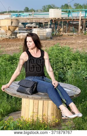 A Girl Sits On A Wooden Reel For Cable. Legs Shod In Summer Sandals. Near A Women's Handbag.