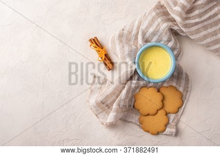 Two Blue Cup With Traditional Indian Masala Chai Tea, Cinnamon Sticks And Cookies On A Linen Napkin