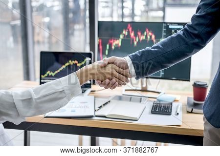 Business Handshake After Discussion And Analyzing Graph Stock Market Trading Good Deal Of Trading To
