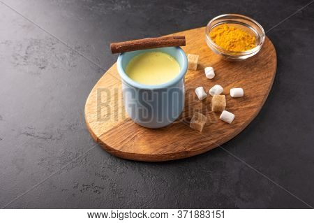 Ceramic Blue Cup With Traditional Indian Masala Chai Tea With Cinnamon And Sugar On Cutting Board. T