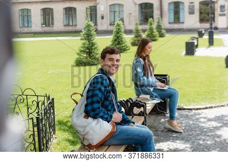 Focus Of Cheerful Student Smiling While Girl Using Laptop Near University Campus, Online Study Conce