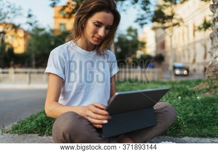 Hipster Girl In A White T-shirt Reads An Ebook On Touchpad While Sitting Outside On Green Grass In T