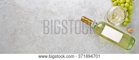 White Wine In A Glass, Bottle, Grapes And Cork On A Gray Stone Table. Top View. Banner. Copy Space O
