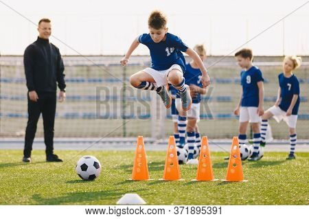 Soccer School Training Unit. Football Boys In Team On Practice Session With Youth Coach. Player Jump