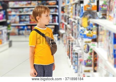 Boy Choosing Toys In Kids Store. Many Toys Around. Kids Shop. Sales, Discounts And Shopping. Cute Bo