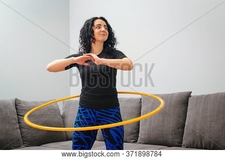 Woman Rotating Hula Hoop. Girl Training At Home. Healthy Sporty Lifestyle. Woman Doing Workout And W