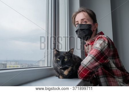 Portrait Of Pensive Woman In Medical Face Mask And Black Cat Looking Out Of Window In Grey Room At H