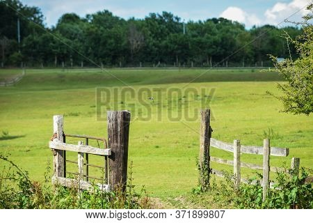 Open Gate To A Field At A Nature Reserve During A Warm Summer Day